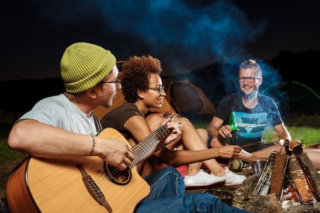 Freunde sitzen in der nähe von lagerfeuer, lächeln, sprechen, ruhen sich aus, spielen gitarre Kostenlose Fotos