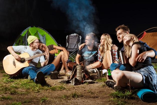 Freunde sitzen in der nähe von lagerfeuer, lächeln, umarmen, ruhen, gitarre spielen Kostenlose Fotos