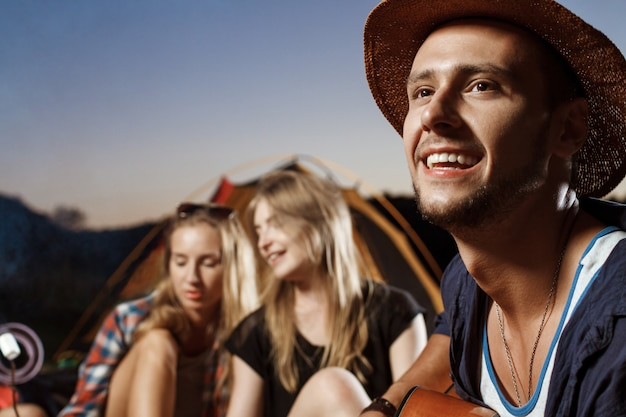 Freunde sitzen in der nähe von lagerfeuer, lächelnd, spielen gitarre camping grill marshmallow. Kostenlose Fotos