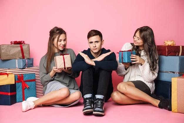 Freunde sitzen unter weihnachtsgeschenken auf rosa Kostenlose Fotos