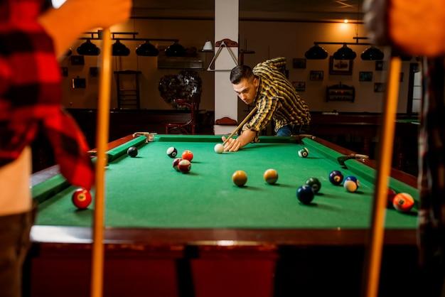 Freunde spielen amerikanisches billard im poolraum. gruppe spielt poolspiel in der sportbar, poolrauminnenraum auf hintergrund Premium Fotos