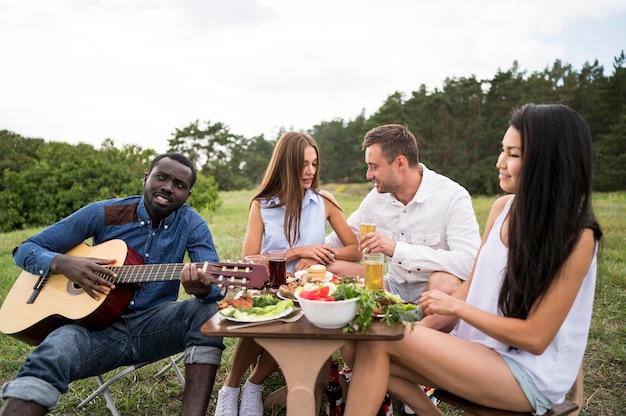 Freunde spielen gitarre und essen beim grillen Premium Fotos