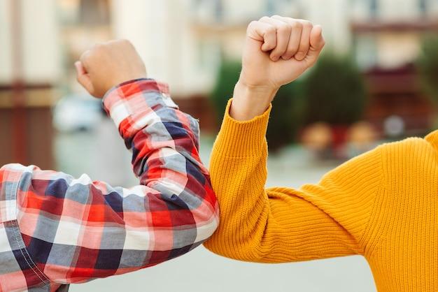 Freunde stoßen im freien an die ellbogen. coronavirus epidemie. soziale distanzierung. bekämpfe das coronavirus. Premium Fotos