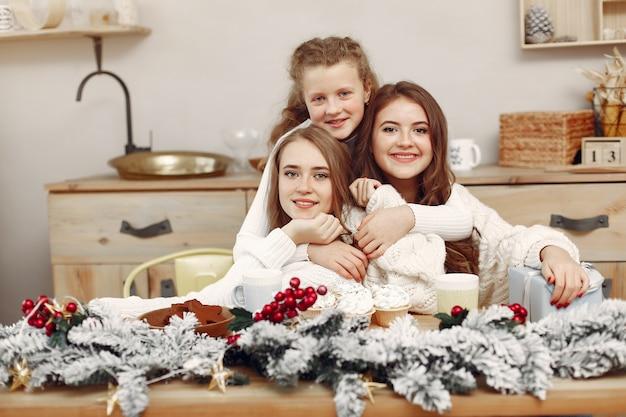 Freunde verbrachten zeit zu hause. zwei mädchen trinken tee. frau in einer weihnachtsmütze. Kostenlose Fotos