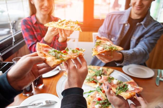 Freunde von klassenkameraden essen pizza in einer pizzeria, schüler beim mittagessen essen fast food Premium Fotos
