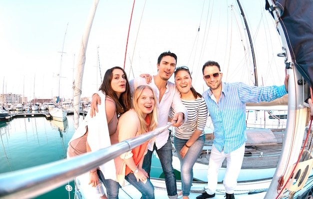 Freundesgruppe, die selfie bild mit stick auf luxus-segelboot-party-reise macht Premium Fotos