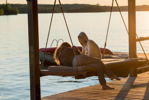 Freundinnen, die auf schwingstuhl am dock, see des holzes, ontario, kanada genießen Premium Fotos
