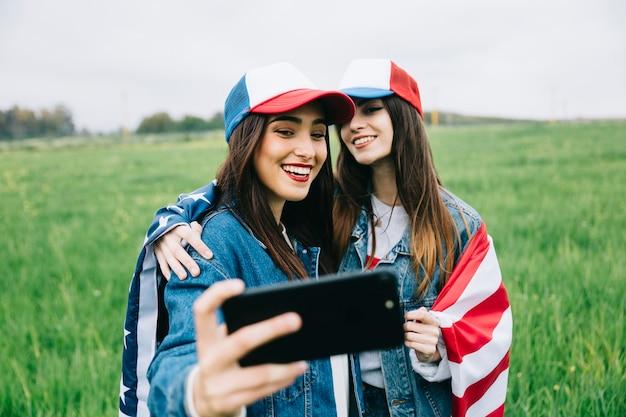 Freundinnen, die auf telefonkamera aufwerfen Kostenlose Fotos