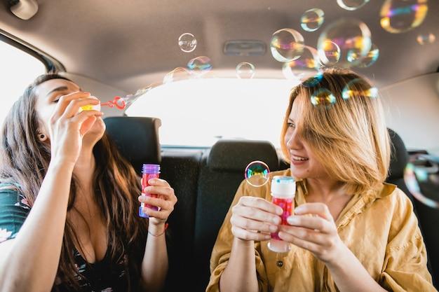 Freundinnen, die blasen im fahrzeug durchbrennen Kostenlose Fotos