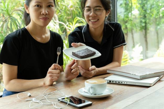 Freundinnen, die kaffeepause mit schokoladenkuchenkuchen in der kaffeestube haben. Premium Fotos