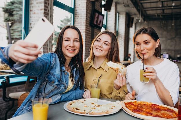 Freundinnen, die pizza an einer bar zu mittag essen Kostenlose Fotos