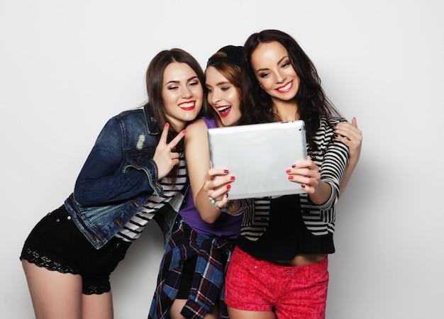 Freundinnen, die selfie mit digitaler tablette nehmen Premium Fotos