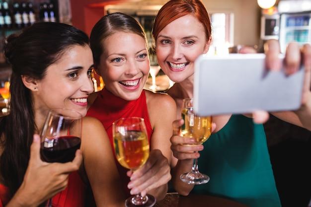 Freundinnen, die selfie mit weinglas im nachtclub nehmen Premium Fotos