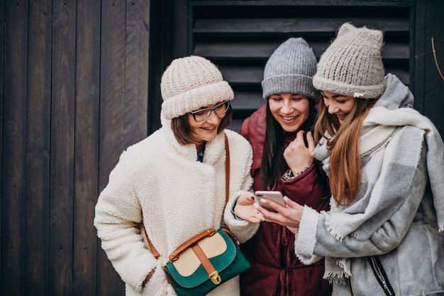 Freundinnen, die sich zusammen zur winterzeit außerhalb der straße treffen Kostenlose Fotos