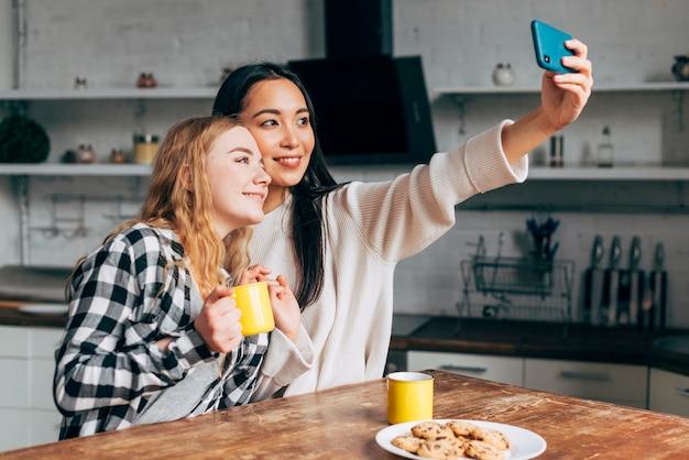 Freundinnen, die zu hause selfies machen Kostenlose Fotos
