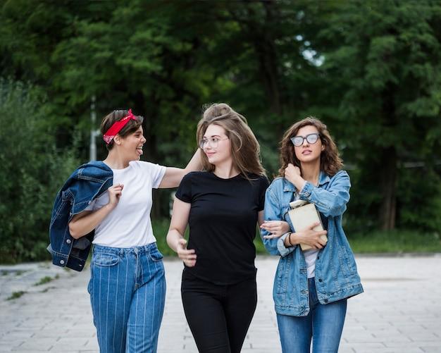 Freundinnen, die zusammen auf parkpflasterung gehen Kostenlose Fotos