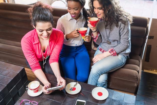 Freundinnen, die zusammen im café sitzen und fotos am intelligenten telefon zeigen Premium Fotos