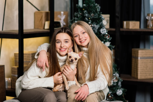 Freundinnen feiern silvester und weihnachten und essen mandarinen auf dem bett. es gibt geschenke und verzierte tannenzweige mit goldenen kugeln. Premium Fotos