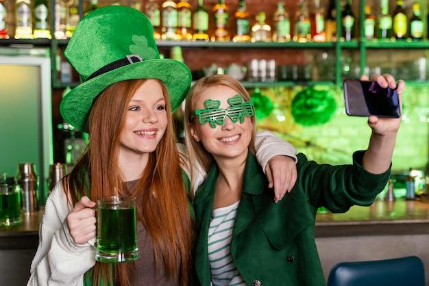 Freundinnen feiern st. patricks tag an der bar und selfie machen Premium Fotos