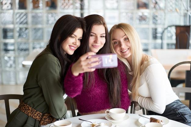 Freundinnen haben spaß im café, trinken tee und machen selfie Premium Fotos