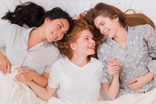 Freundinnen ins bett gelegt und händchen haltend