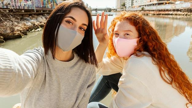 Freundinnen mit gesichtsmasken im freien nehmen ein selfie zusammen Kostenlose Fotos