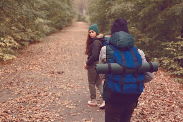 Freundinnen reisende mit rucksäcken gingen im wald wandern. Premium Fotos