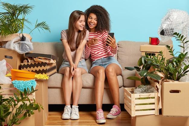 Freundinnen sitzen auf der couch, umgeben von kisten Kostenlose Fotos