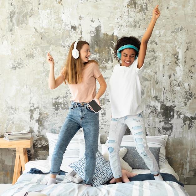 Freundinnen tanzen im bett, während sie musik über kopfhörer hören Kostenlose Fotos