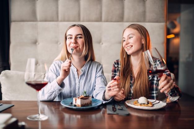 Freundinnen trinken getränke und essen süße desserts im café. schokoladenkuchen und alkohol auf dem tisch Premium Fotos