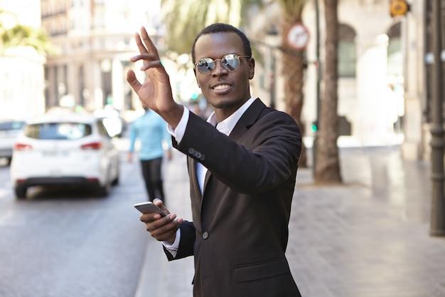 Freundlich aussehender erfolgreicher junger afroamerikanischer unternehmer im eleganten schwarzen anzug und in der brille, die sms auf handy und hand anheben, während taxi heraufhagend, auf straße in der städtischen umgebung stehend Kostenlose Fotos