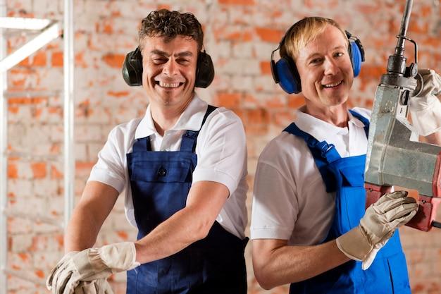 Freundliche bauarbeiter mit lufthammer Premium Fotos