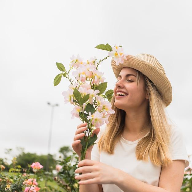 Freundliche dame im hut mit weißer blüte Kostenlose Fotos