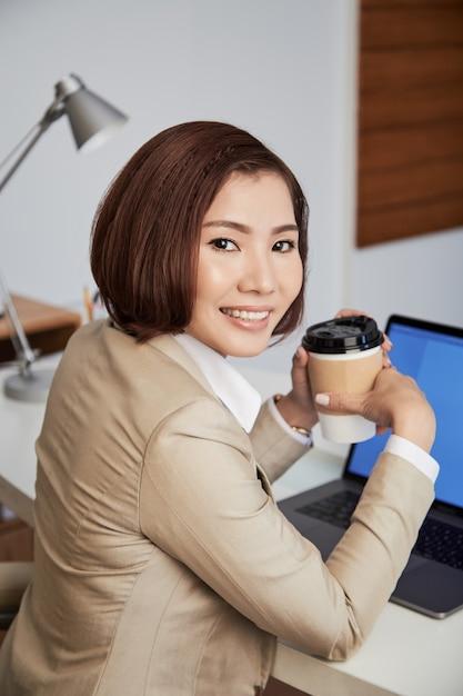 Freundliche ethnische geschäftsfrau mit kaffee Kostenlose Fotos