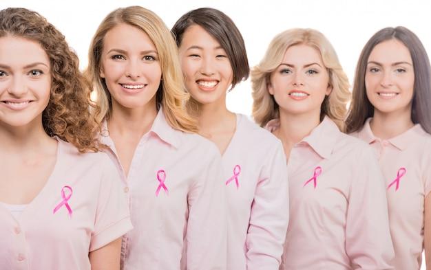 Freundliche frauen, die rosafarbene farbbänder tragen, um brust zu stützen. Premium Fotos