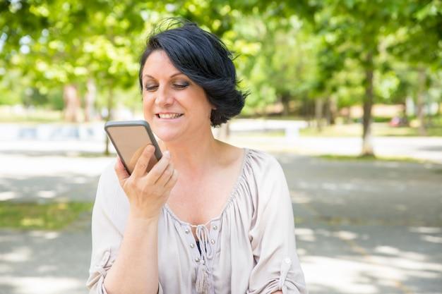 Freundliche glückliche frau, die auf lautsprecher spricht Kostenlose Fotos