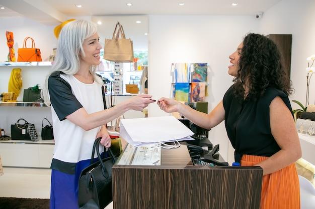 Freundliche kassiererin, die dem kunden nach der zahlung eine kreditkarte gibt, sich für den kauf bedankt und lächelt. mittlerer schuss. einkaufskonzept Kostenlose Fotos
