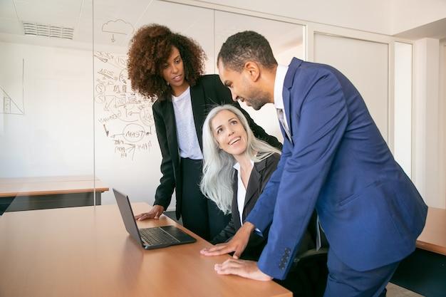 Freundliche kollegen diskutieren projekt im büroraum und lächeln. erfolgreiche grauhaarige content-geschäftsfrauen, die am tisch sitzen und mit partnern sprechen. teamwork-, geschäfts- und managementkonzept Kostenlose Fotos