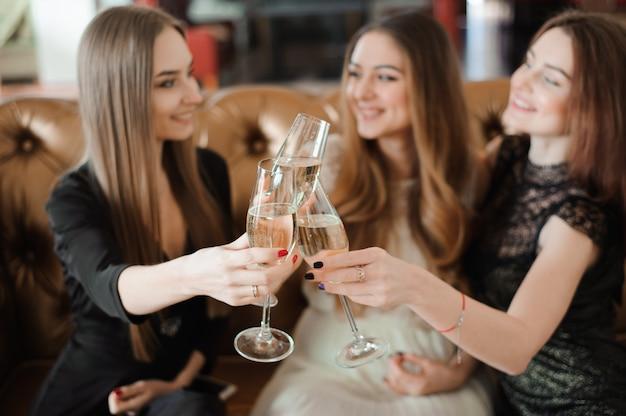 Freundliche mädchen, die gläser champagner an der party klirren Premium Fotos