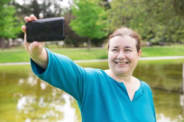 Freundliche plus sortierte frau, die selfie im park nimmt Kostenlose Fotos