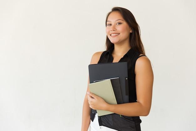 Freundliche studentin mit faltblatt und lehrbüchern Kostenlose Fotos