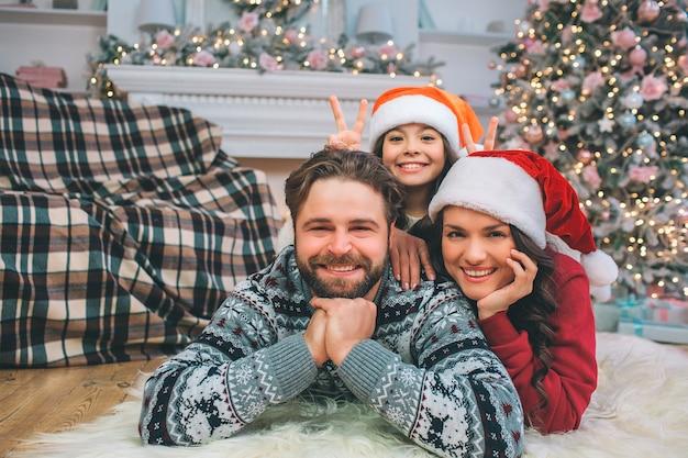 Freundliche und positive junge familie, die auf boden liegt und gerade schaut. sie lächeln. junge frau und mädchen sind hinter mann. sie tragen weihnachtsmützen. Premium Fotos