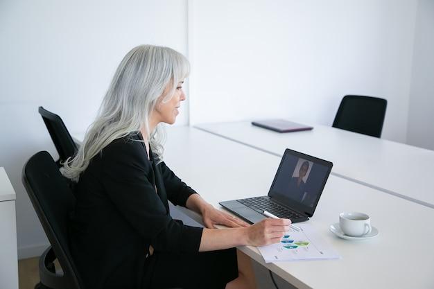 Freundliche weibliche büroangestellte, die mit kollegin über video-chat auf laptop spricht, während sie am tisch mit tasse kaffee sitzt und diagramm analysiert. online-kommunikationskonzept Kostenlose Fotos