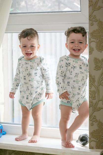 Freundliche zwillinge - brüder stehen auf einem fensterbrett Premium Fotos