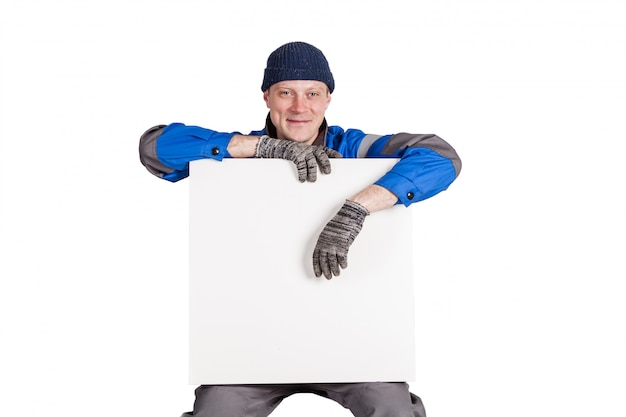 Freundlicher bauarbeiter, der ein leeres, weißes zeichen hält. isoliert auf weiss Premium Fotos