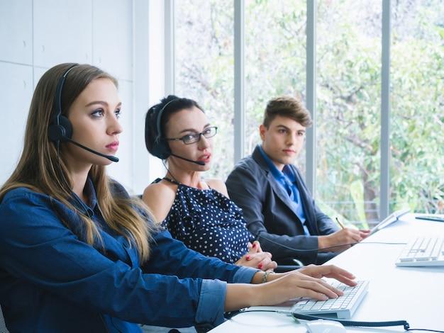 Freundlicher bedienerteamagent mit den kopfhörern, die in einem call-center arbeiten Premium Fotos