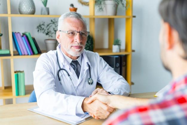 Freundlicher doktor, der hand des patienten rüttelt Kostenlose Fotos