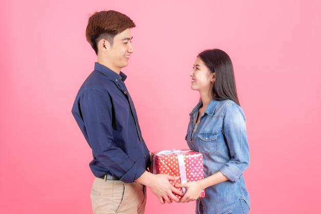Freundlicher jugendmann und frau des porträts, sind sie rote geschenkbox des platzes und lächeln mit lustigem, jugendlichem asiatischem paarkonzept Kostenlose Fotos