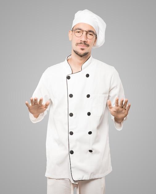 Freundlicher junger koch, der eine geste der ruhe tut Premium Fotos