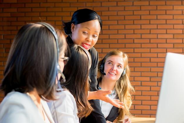 Freundlicher schwarzer geschäftsfrauüberwacher, der mit ihrem team im kundenkontaktcenter arbeitet Premium Fotos